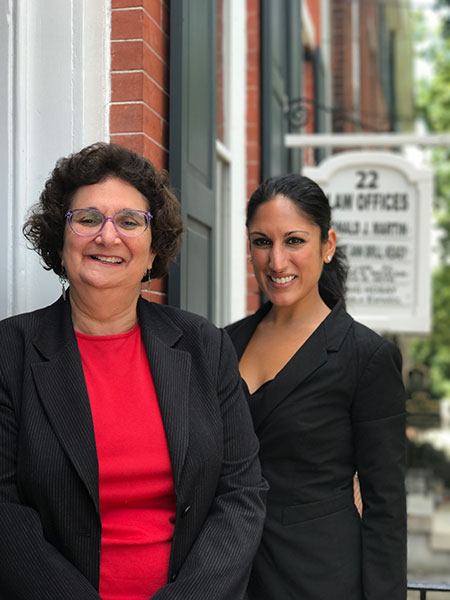 Portrait of Sharon and Anita in from of AMC Law office building.